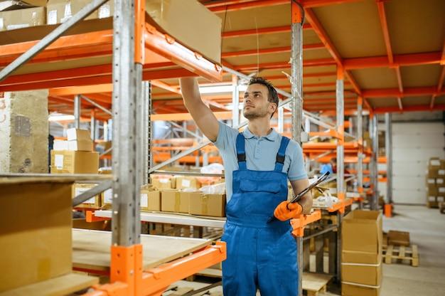 Fietsfabriek, werknemer controleert vak op de plank in het magazijn van fietsen. mannelijke monteur in uniform bij de packs met fietsonderdelen