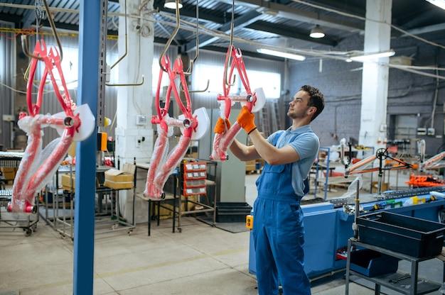 Fietsfabriek, werknemer houdt fietsframe. mannelijke monteur in uniform installeert fietsonderdelen, lopende band in werkplaats