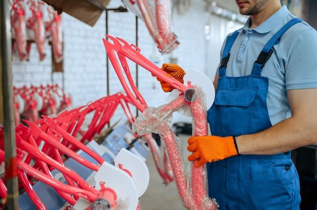 Fietsfabriek, werknemer houdt fietsframe van roze kind vast. mannelijke monteur in uniform installeert fietsonderdelen, lopende band in werkplaats