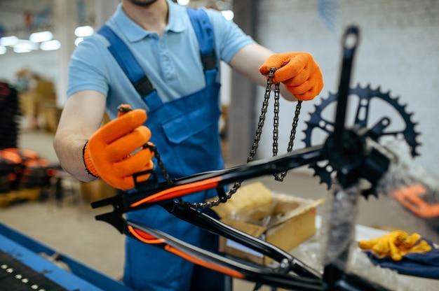 Fietsfabriek, werknemer houdt fietsketting bij lopende band. mannelijke monteur in uniform installeert fietsonderdelen in de werkplaats