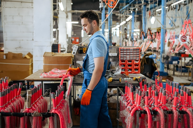 Fietsfabriek, werknemer houdt fietsvork van roze kind vast. mannelijke monteur in uniform installeert fietsonderdelen, lopende band in werkplaats