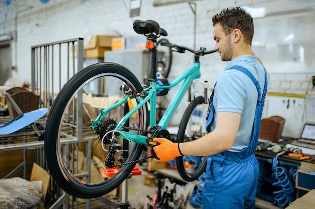 Fietsfabriek, werknemer houdt mountainbike. mannelijke monteur in uniform installeert fietsonderdelen, lopende band in werkplaats