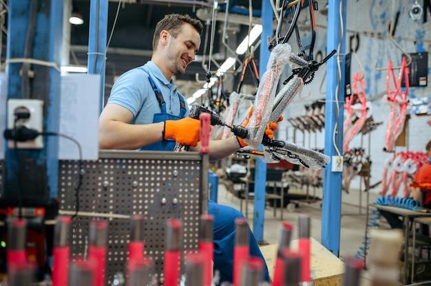 Fietsfabriek, werknemer houdt roze kinderfiets vast. mannelijke monteur in uniform installeert fietsonderdelen, lopende band in werkplaats