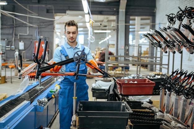Fietsfabriek, werknemer houdt zwart tienerfietsframe. mannelijke monteur in uniform installeert fietsonderdelen, lopende band in werkplaats