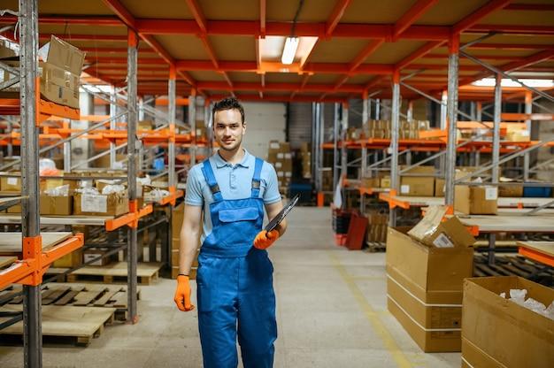 Fietsfabriek, werknemer in de buurt van de plank in het fietsenmagazijn. mannelijke monteur in uniform bij de packs met fietsonderdelen, lopende band in werkplaats