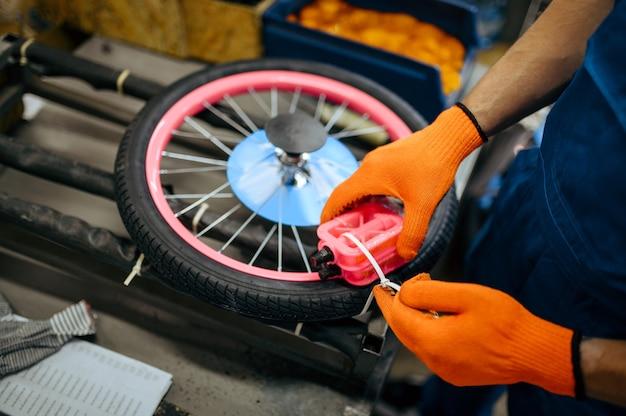 Fietsfabriek, werknemer pakt kinderfiets in. mannelijke monteur in uniform installeert fietsonderdelen, lopende band in werkplaats