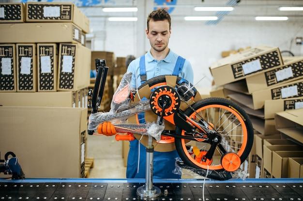 Fietsfabriek, werknemer pakt tienerfiets in. mannelijke monteur in uniform installeert fietsonderdelen, lopende band in werkplaats