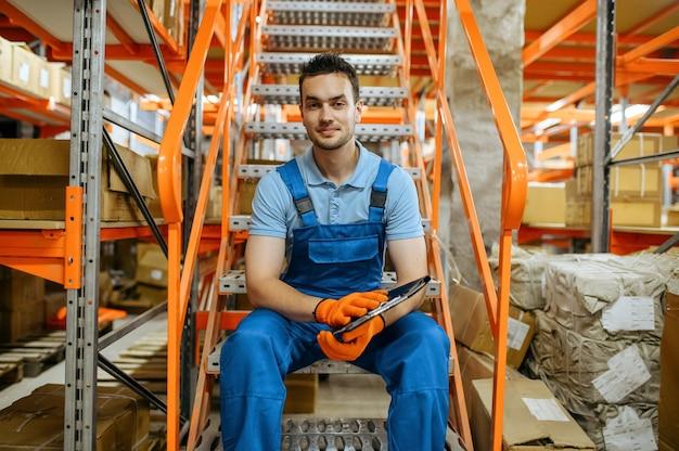 Fietsfabriek, werknemer zittend op de trap in fietsenmagazijn. mannelijke monteur in uniform bij de packs met fietsonderdelen
