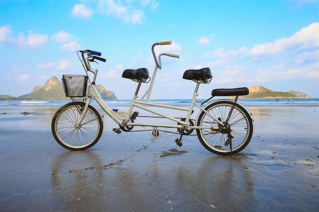Fietsparkeren achter elkaar op het strand met zijn bezinning