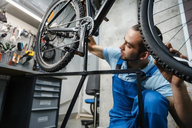 Fietsreparatie in de werkplaats, man controleert het wiel op speling
