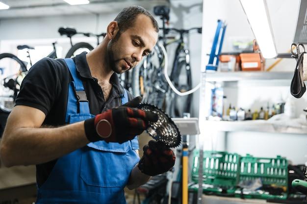 Fietsreparatie in werkplaats, man installeert stercassette