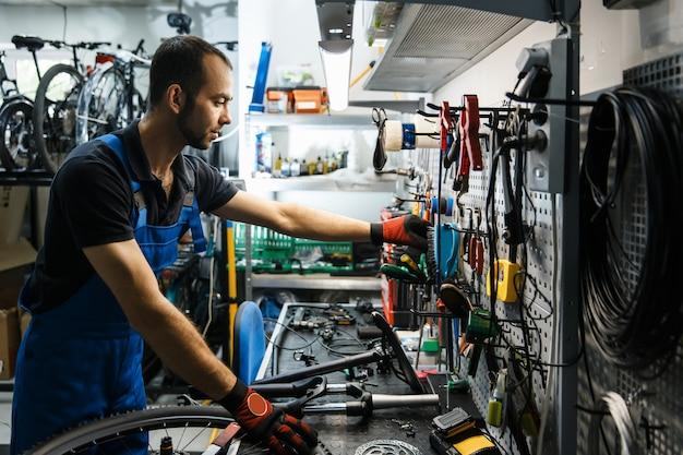 Fietsreparatie in werkplaats, man neemt gereedschap uit de plank