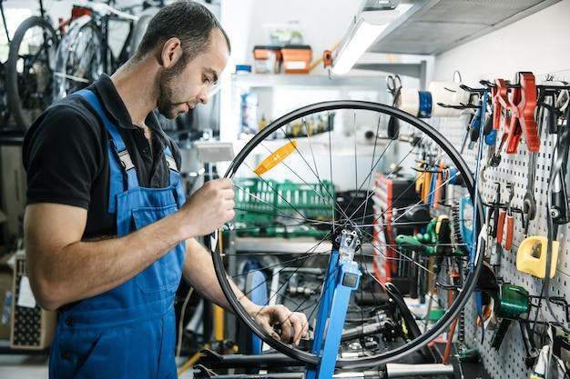 Fietsreparatie in werkplaats, man werkt met wiel