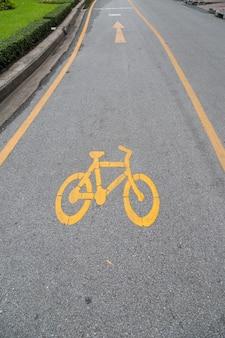 Fietsstegen en geel fietssymbool, fietssteeg op openbare parktuinachtergrond