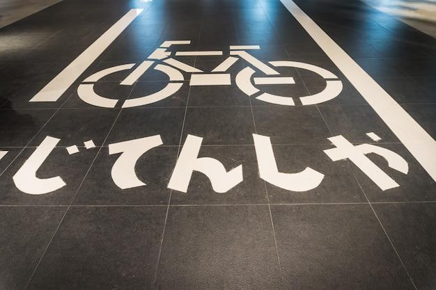 Fietssymbool op stadsstraat met licht (vertaal japanse tekst