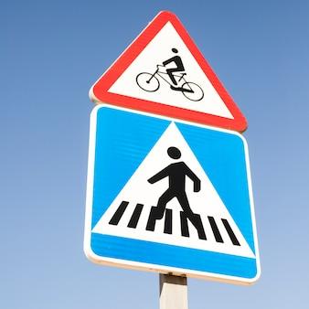 Fietswaarschuwingsbord over de moderne vierkante voetgangersoversteekplaatsverkeersteken tegen blauwe hemel