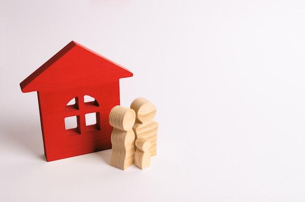 Figuren van mensen staan in de buurt van een houten huis. een jong gezin staat in de buurt van hun huis.