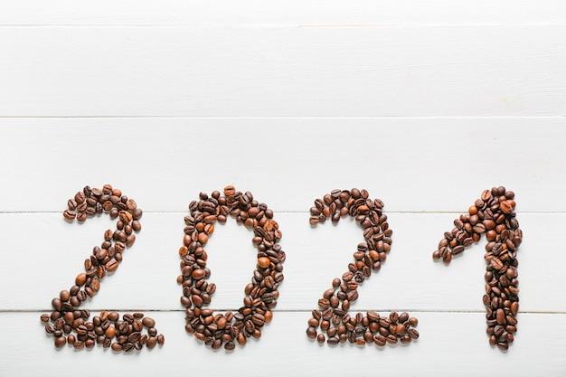 Figuur 2021 gemaakt van koffiebonen op wit houten