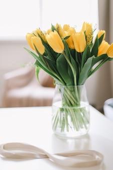 Figuur acht van beige lint met mooie gele tulpen in een vaas.