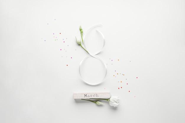 Figuur acht van wit lint met mooie witte eustomas op een witte achtergrond met gekleurde confetti, plat leggen. 8 maart, internationale vrouwendag.