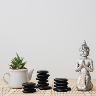 Figuur van boeddha naast stapels van vulkanische stenen en pot