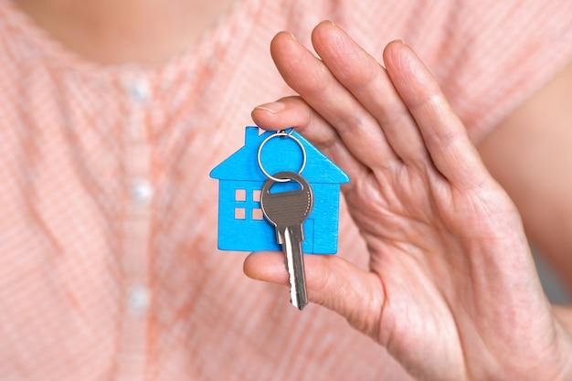 Figuur van een blauw mini-huisje met de sleutels in de hand van een persoon