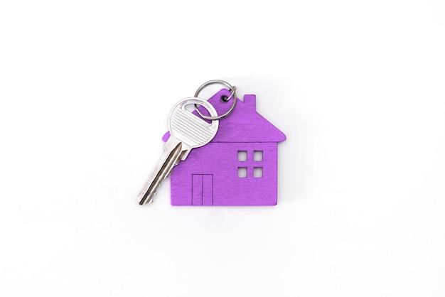 Figuur van een minihuis van paarse kleur met sleutels op een afgelegen witte achtergrond.