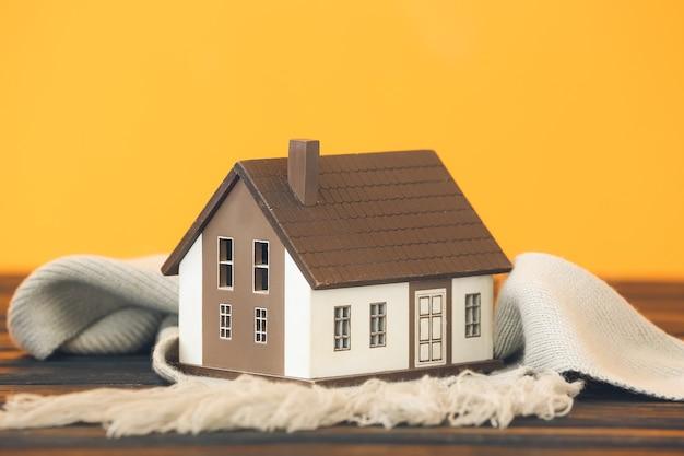 Figuur van huis en warme sjaal op tafel. concept van het stookseizoen