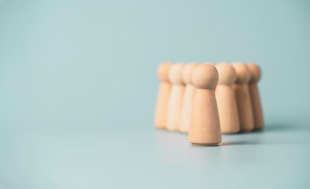 Figuur voor andere houten figuren op blauwe achtergrond, promotie naar leiderschap en managementgroeiconcept.