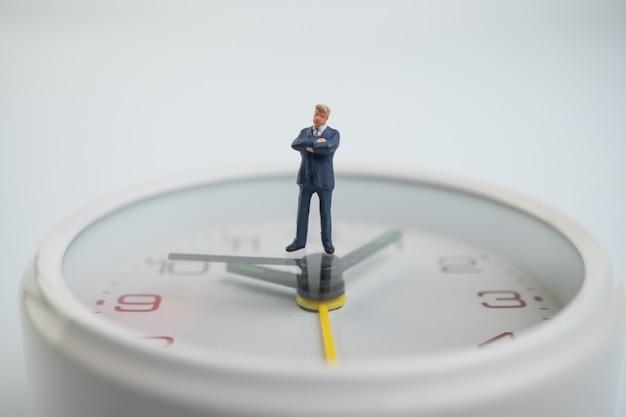 Figuur zakenlieden denken en staan op de witte wijzerplaat naast de wijzerplaat met de tijd.