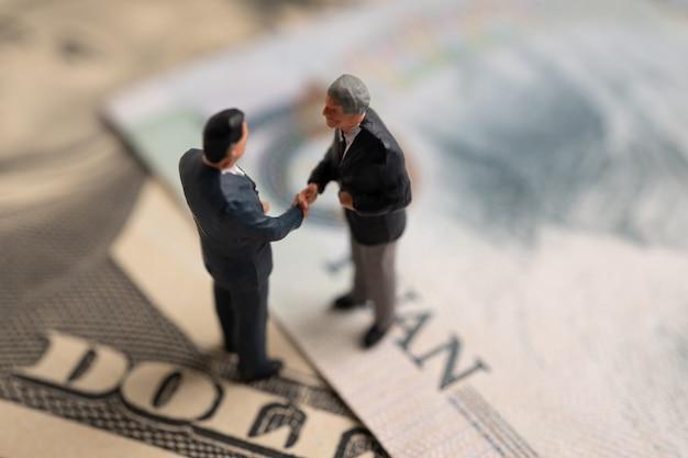 Figuurzakenman die zich op amerikaanse dollar en yuan-bankbiljet bevinden, houden handen aan succes in handelsovereenkomsten