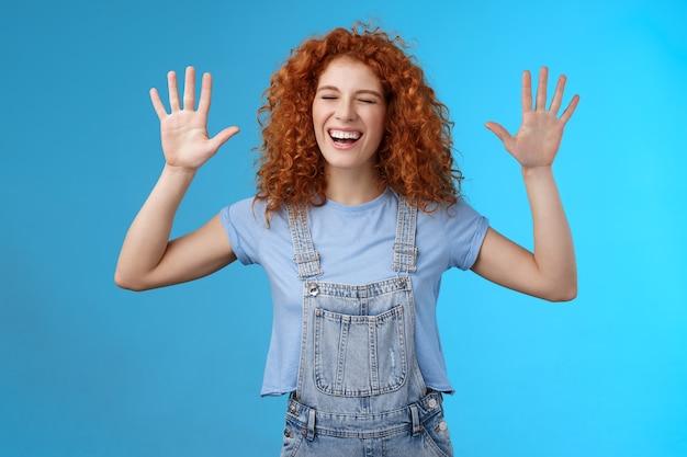 Fijn dat je gewonnen hebt. vrolijke zorgeloze speelse aantrekkelijke roodharige krullende vriendin die plezier heeft hardop lachen vreugdevolle handen omhoog overgave gek rond genieten van coole geweldige tijd doorbrengen met vriend. ruimte kopiëren