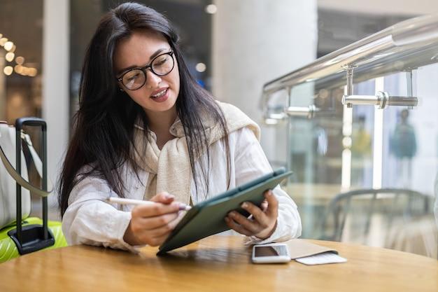 Fijne aziatische jonge vrouw die in een café zit met een koffiekopje dat aantekeningen maakt en geniet van een pauze