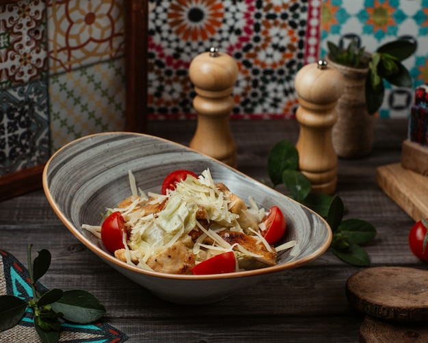 Fijne caesarsalade met fijngehakte parmezaanse kaas en zoete kersen in een rustieke kom