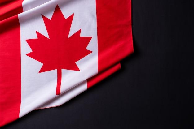 Fijne canada-dag. vlaggen van canada tegen een zwarte achtergrond. kopieer ruimte.