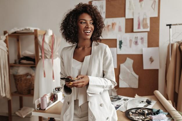 Fijne charmante donkerbruine, krullende brunette vrouw in witte jas, stijlvolle top lacht oprecht, kijkt weg, houdt telefoon vast