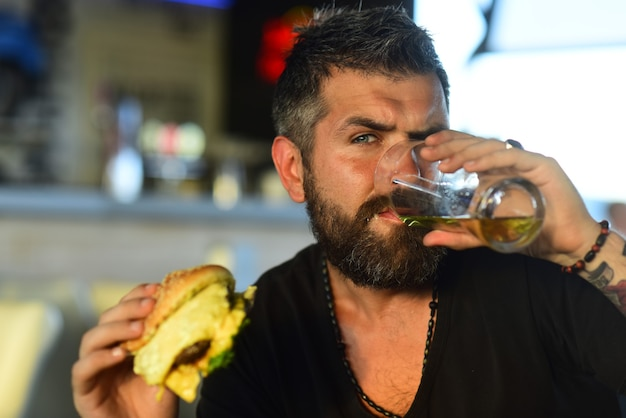 Fijne elegante man die bier drinkt portret van een knappe jongeman die een tapbier proeft, geniet ervan in de pub