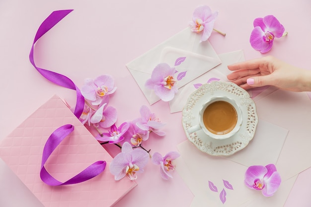 Fijne flatlay-compositie met 's ochtends kopje koffie of cappuccino, letters, roze geschenkpapierzak en orchideebloemen op lichtroze oppervlak. vrouw hand houdt een kopje koffie. prachtig ontbijt