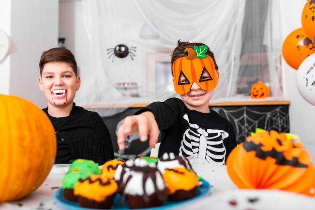 Fijne halloween! aantrekkelijke jonge jongen met zijn broer bereiden zich voor op halloween-feest. broers in kostuums vermaken zich met pompoenen en cupcakes.