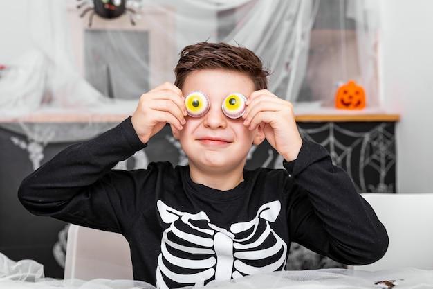 Fijne halloween! de aantrekkelijke jonge jongen in kostuum heeft pret en speelt met enge ogendecoratie