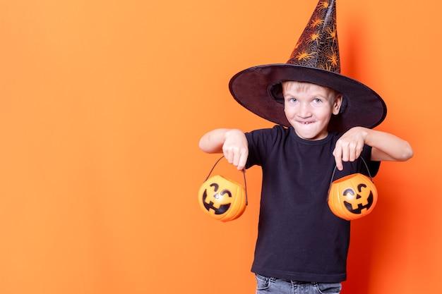 Fijne halloween. enge halloween-kinderen. vrolijke angstaanjagende jongensemmers met snoepjes in pompoenlantaarn voor halloween op oranje achtergrond, kopieer ruimte. trick or treat is een halloween-traditie.