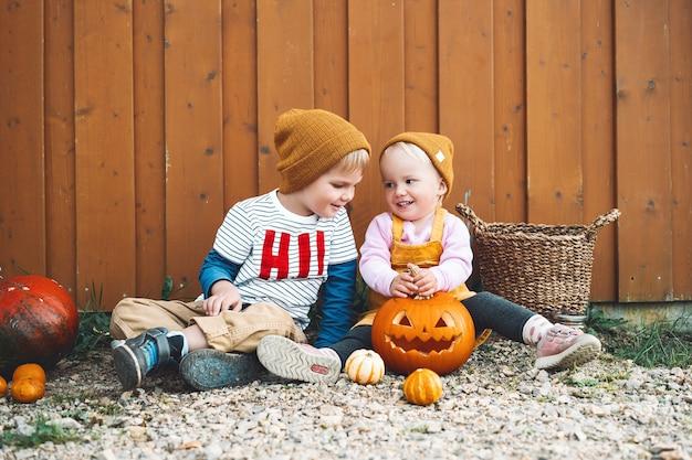 Fijne halloween! foto van herfststemming met stijlvol meisje en jongen die plezier hebben op het platteland. kinderfeest en viering concept. schattige kleine kinderen met pompoenen op houten schuur achtergrond buiten.