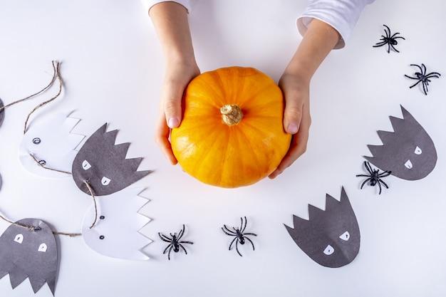Fijne halloween. kind hand met kleine pompoen
