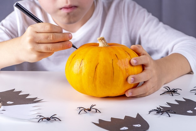 Fijne halloween. kind hand trekt gezicht op pompoen met marker