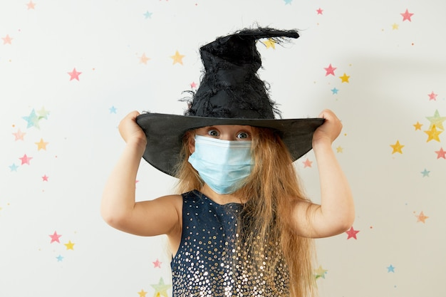 Fijne halloween . klein meisje kind in heks carnaval kostuum en gezicht bescherming masker.