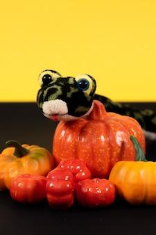 Fijne halloween. veel pompoenen met een groene slang op een gele achtergrond