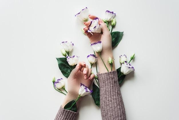 Fijne handen en lentebloemen van eustoma liggen op de witte tafel.