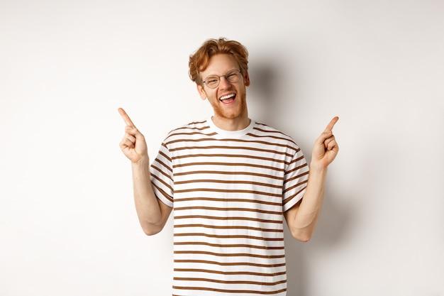 Fijne hipster-man met rood rommelig haar en een bril die lacht, met zijn vingers omhoog wijst, verkooppromotie laat zien, witte achtergrond