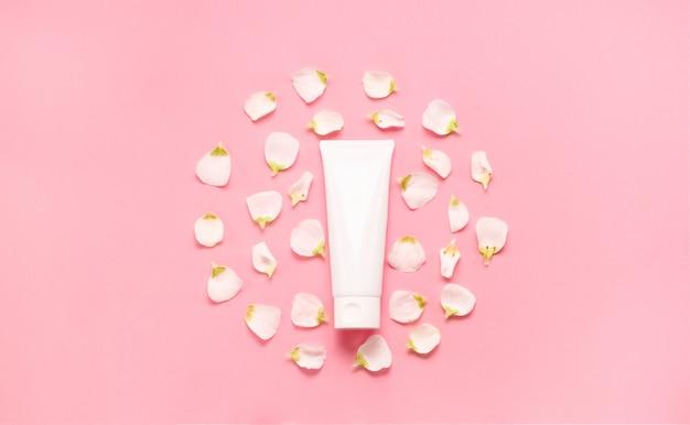 Fijne huidverzorging cosmetische vrouwelijke flatlay. bovenaanzicht creatieve compositie van gezichtscrème, flessen en potten met cosmetica en bloemen laat op abstracte achtergrond
