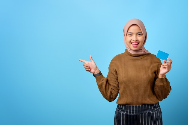 Fijne jonge aziatische vrouw die een creditcard vasthoudt en met de vinger wijst om ruimte op een blauwe achtergrond te kopiëren
